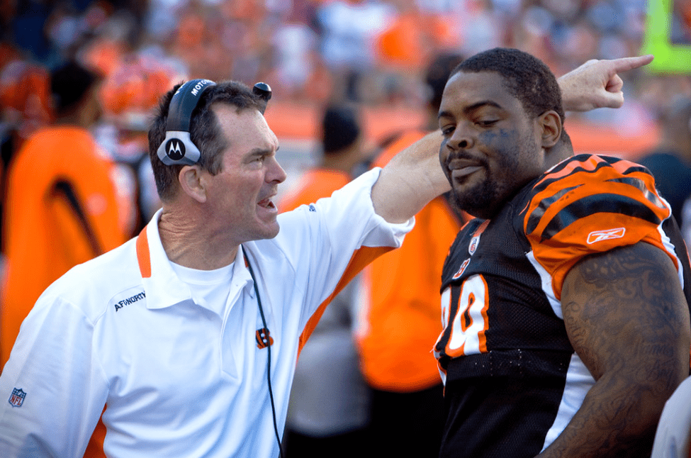 Cincinnati Bengals Defensive Coordinator Mike Zimmer yells at player Tank Johnson (#99 - Defensive Tackle). Johnson looks obviously upset.