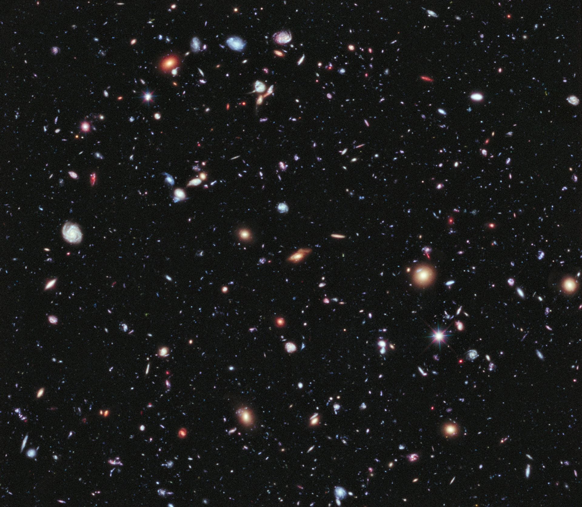 Several hundred galaxies of all shapes and colors shine against a black background.