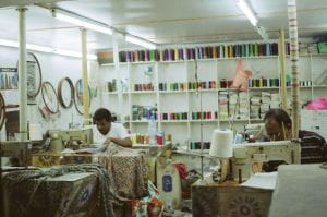 Two people working in a sweat shop sewing clothes.