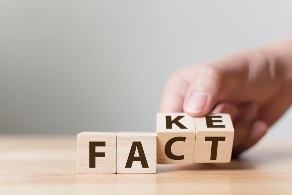 "(wooden blocks that spell out the word fact, but show ""ke"" on the back of ""ct"" to make it look as though it could also spell fake"
