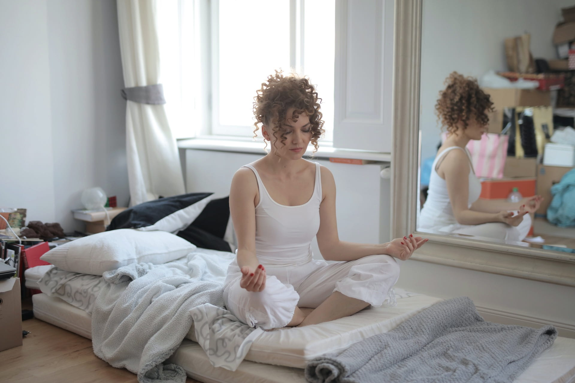 [calm-woman-in-lotus-pose-meditating-after-awakening-at-home]