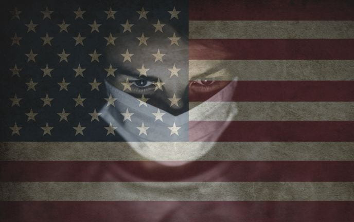 A silhouette of a young man wearing a white mask is superimposed over the American flag.
