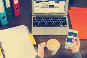 This image is of a first person view of a desk with an opened lined notebook on the left, a laptop open in the center, a person's left hand is holding a cup of coffee, and the right hand is holding a phone opened with the Facebook login screen.