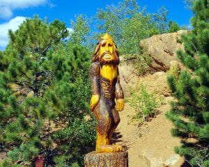 A statue of bigfoot sits in the middle of a forest with trees flanking it on both sides and brown-grayish rocks behind it.