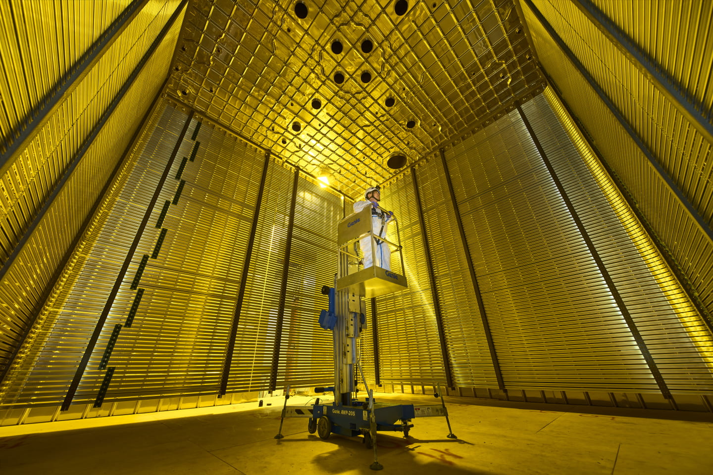 [A scientist in white clothes on a lift surveys the inside of a gold-coated and box-shaped detector for neutrinos.]