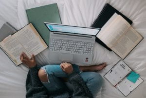 aerial view of someone wearing jeans who is studying in front of laptop sitting criss-crossed with several books laid to their side against white sheets