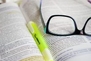 yellow highlighter set on an open textbook with black glasses on top of it
