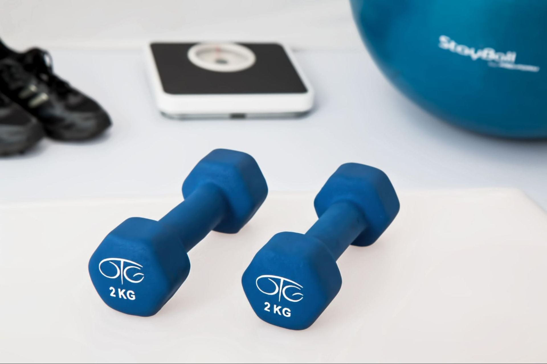 A photograph of at home workout equipment. It includes a blue set of dumbbells, a black pair of sneakers, a scale, and a blue exercise ball laid out on white flooring.