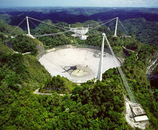 [An overhead view of the massive Arecibo telescope built into a natural sinkhole. The green Puerto Rican forests can be seen surrounding the telescope dish.]