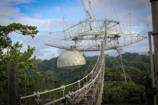 The receiver for the Arecibo telescope. A large white half dome is suspended in the air by a complex set of wires and struts. Behind the receiver the Puetro Rican forests can be seen.