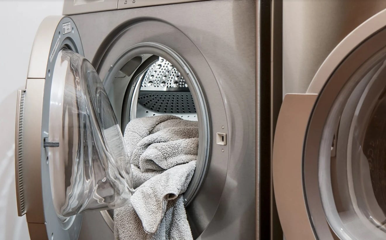 A laundry machine that is not currently in use with an open door and towels hanging out of it.