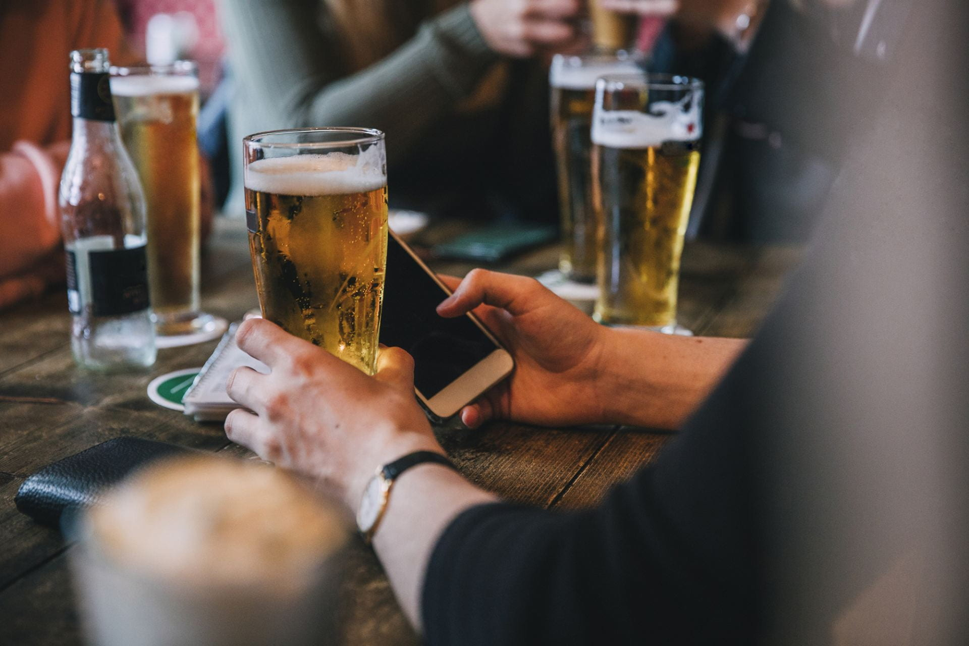 [A photo of a person drinking a beer while also on their mobile phone.]