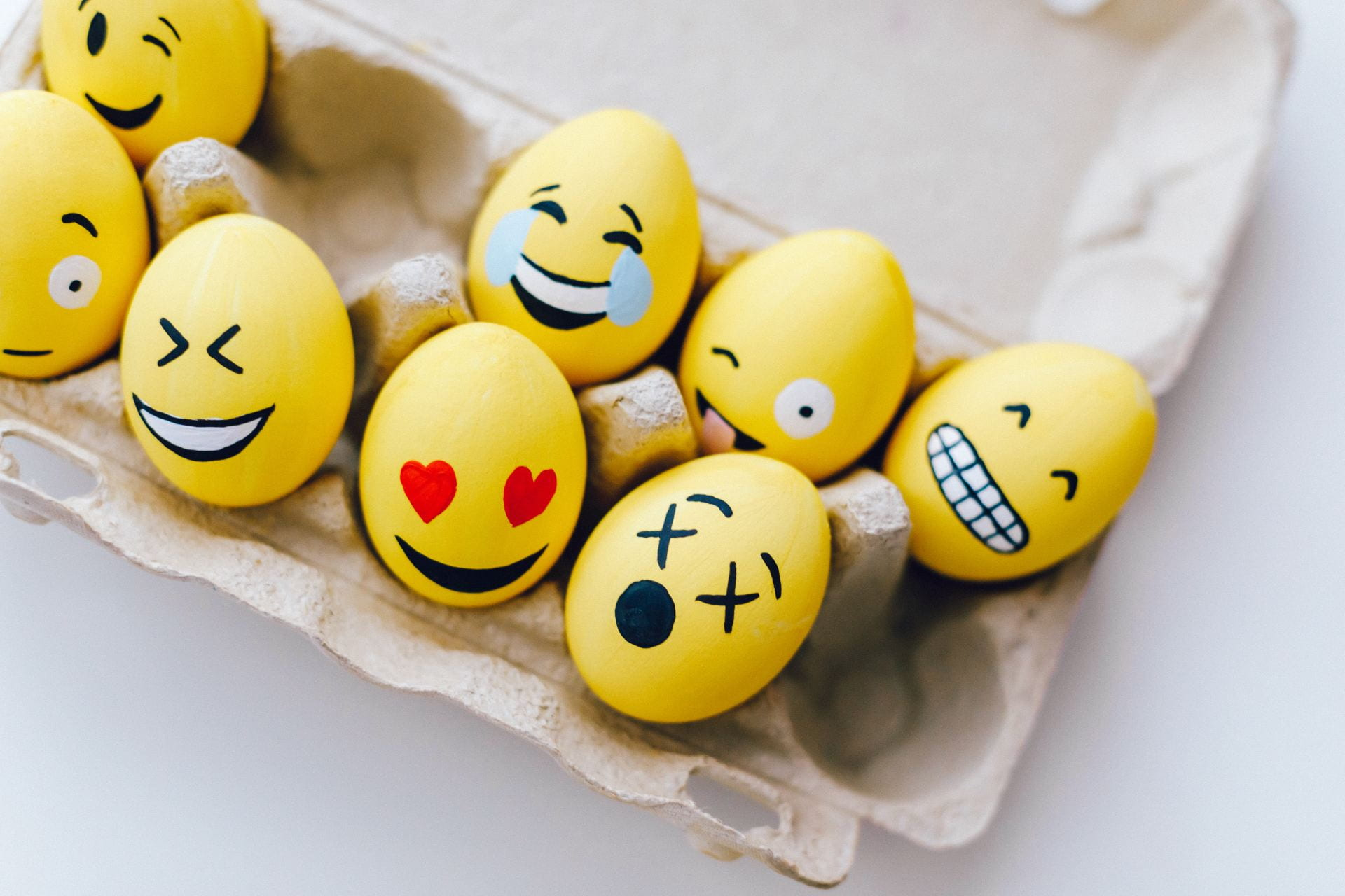 [Alt-text: Yellow painted eggs with various facial expressions.]