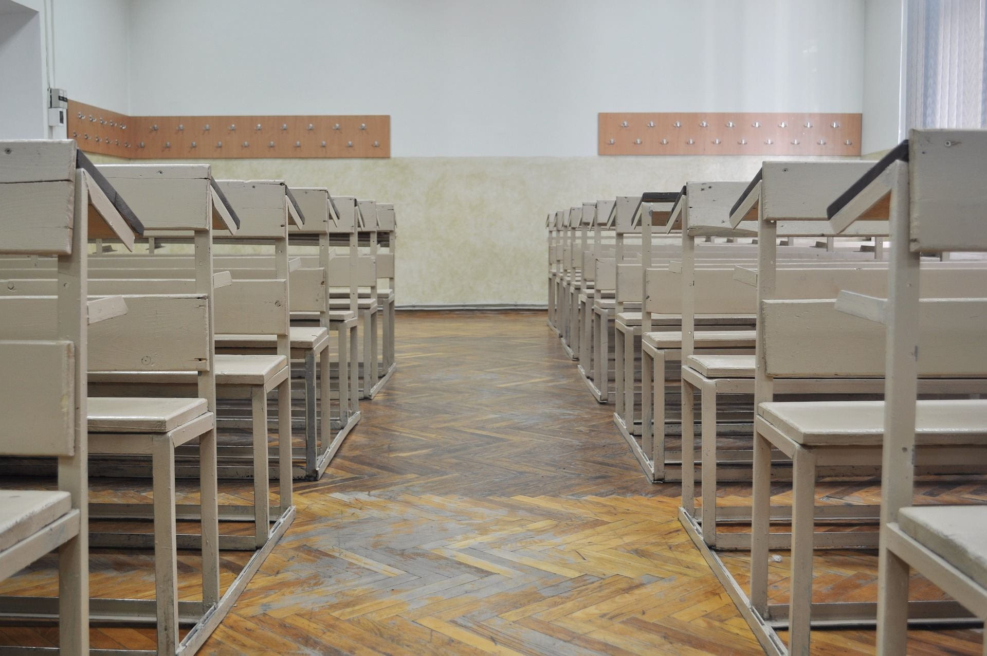 Pictured is an empty classroom with all the chairs facing a blank white board