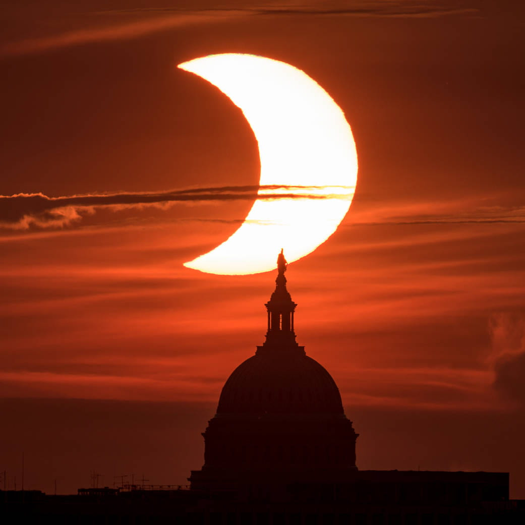 [The sun rises behind the United States Capitol Building during a partial solar eclipse.]