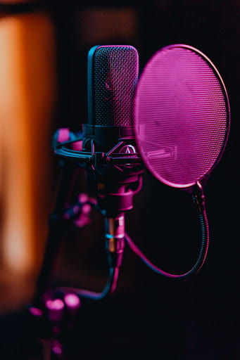 [Recording microphone with pop filter lit in soft purple light.]