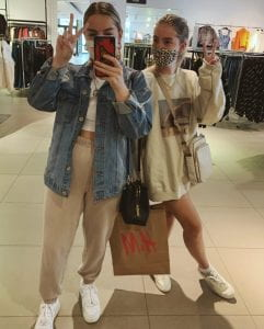 two women inside clothing store hold up peace sign with fingers