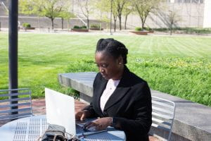 Moyo works at a laptop at an outdoor table.