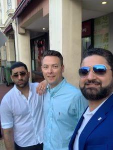 Drs. Aditya Ahlawat, Hattaway and Abhishek Kapila stand on a street in Singapore.