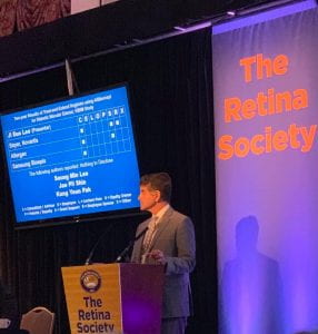 Dr. Ciulla is standing at a podium in front of a banner that reads The Retina Society.