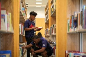Two male students look through books in the IUPUI library.