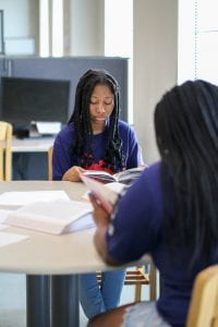 Two female students from Upward Bound read books at a table.