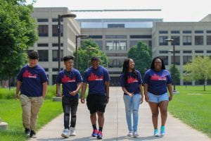 Five Upward Bound students walk through campus together, laughing.
