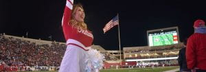 dance team member smiles, waves from sidelines during game