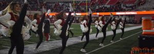 dance team kicking high during a halftime show on field