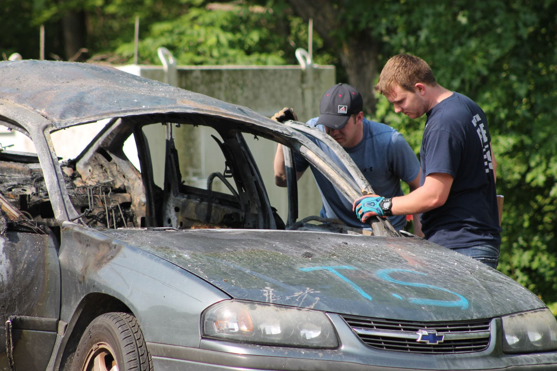Two students stand beside the burned out remains of a car that had a bomb explode inside of it.