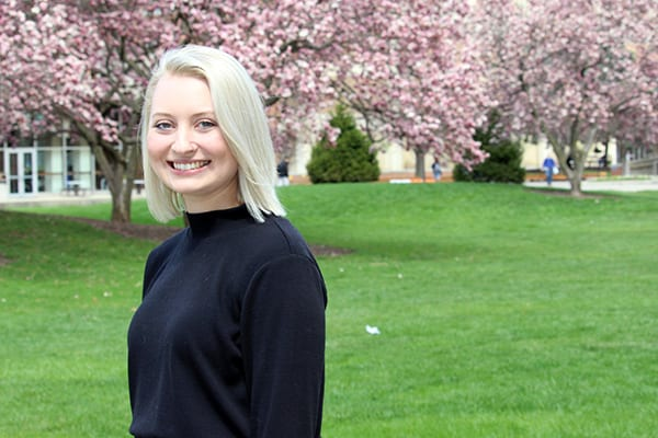 Morgan Farnworth standing in front of magnolia trees on campus
