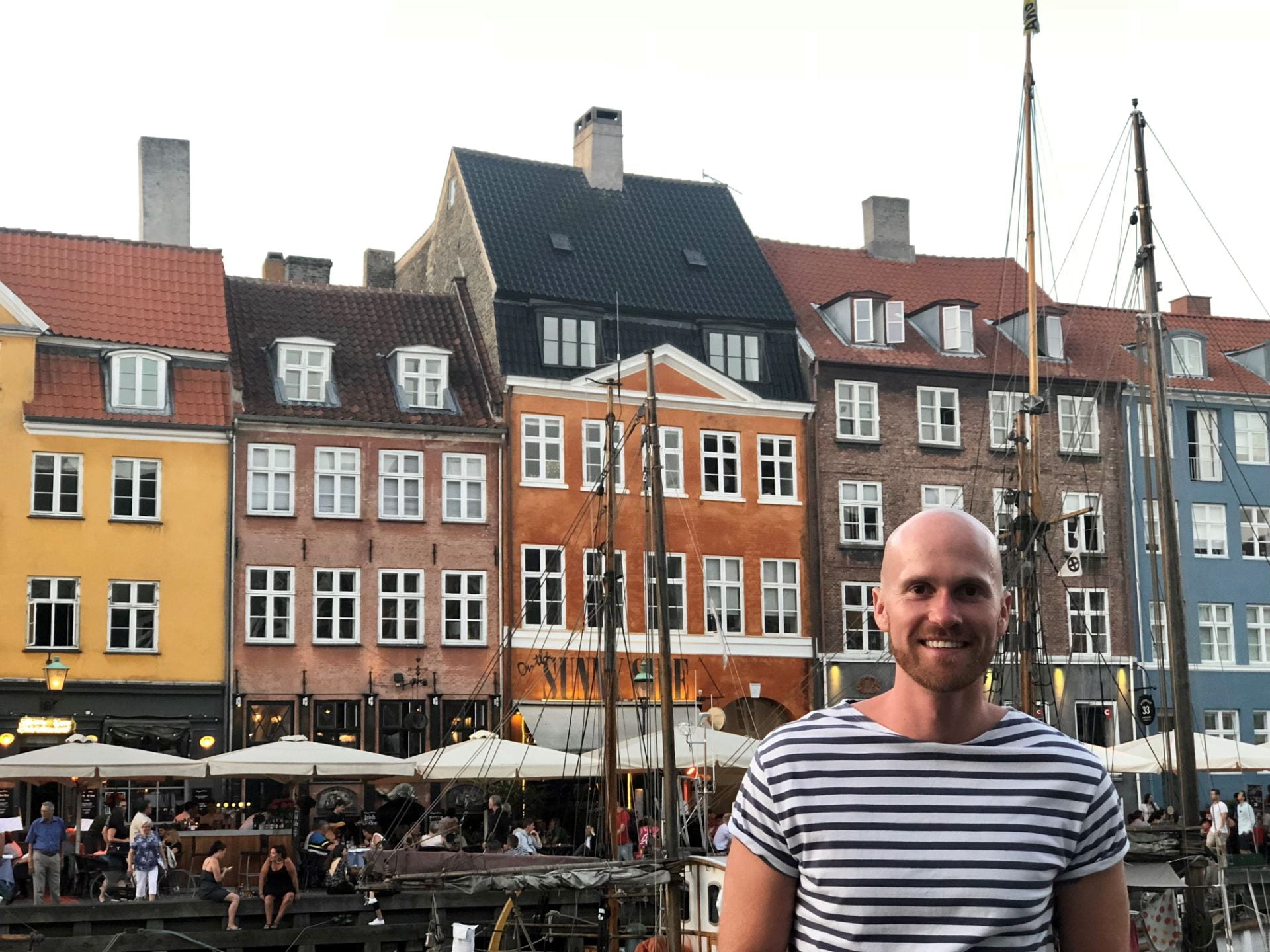 Jason Sprinkle stands in front of colorful houses in Denmark