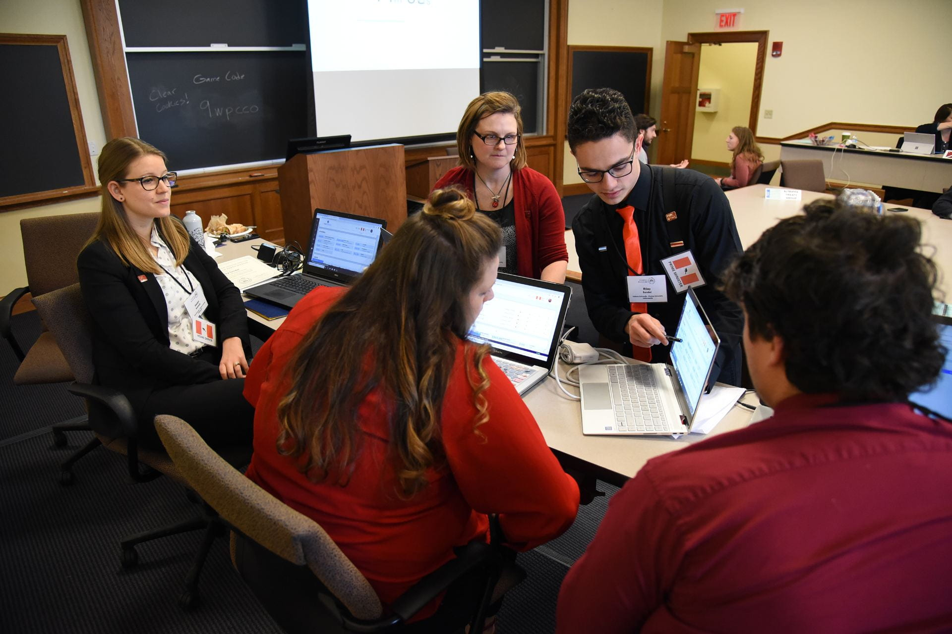 Students sit together at a table going through documents and reading through policy options, discussing possible solutions to simulated migration issues.