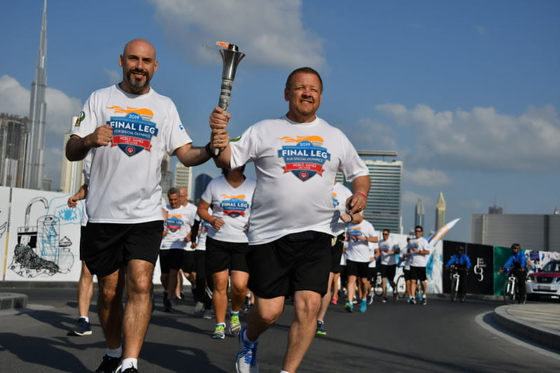 Scott Teal runs through the streets of Abu Dhabi carrying the torch for the Special Olympics' Law Enforcement Torch Run in 2019.