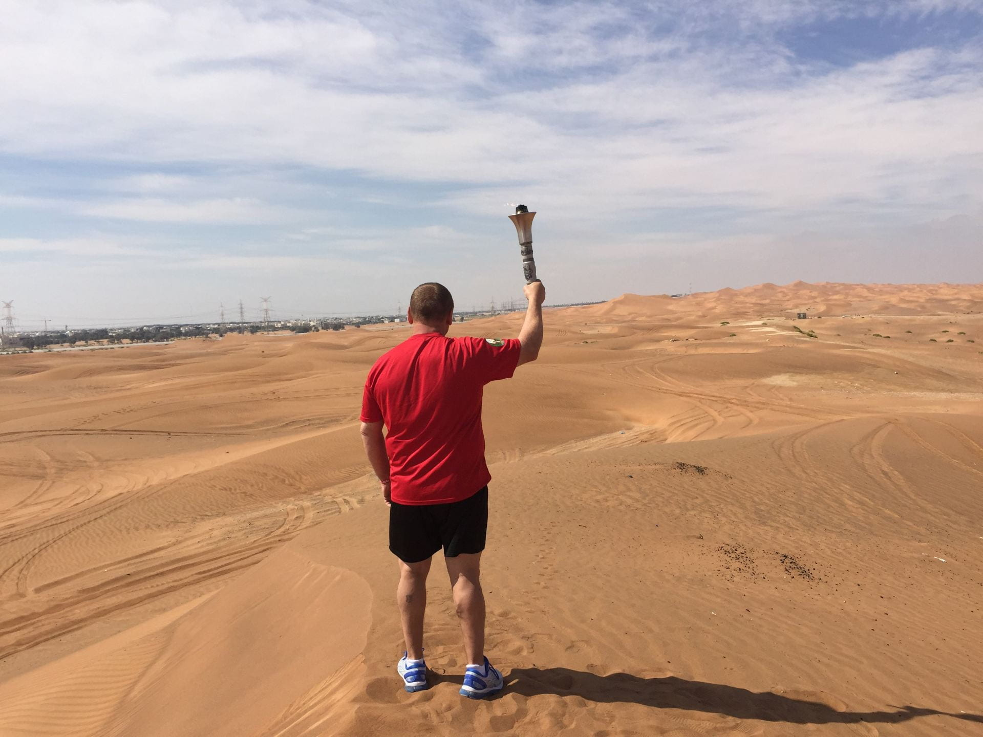 Scott Teal stands in the middle of a desert, wearing a red shirt. With his back to the camera, he holds us the Olympic Torch he will carry during the Law Enforcement Torch Run.