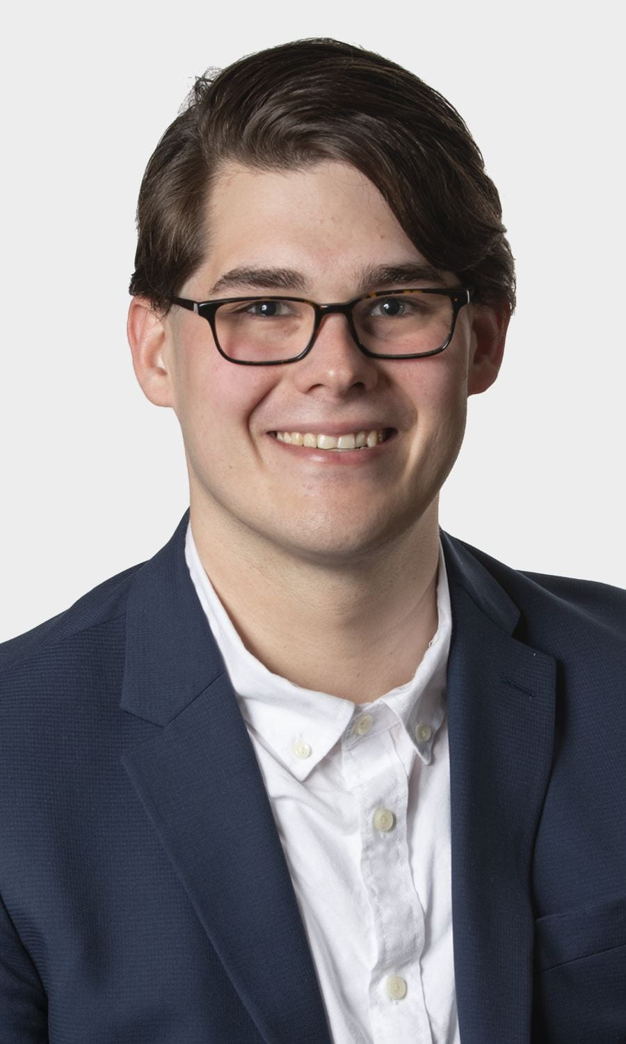 Kyle Casteel smiles, wearing a white button-up shirt, blue blazer and dark glasses.