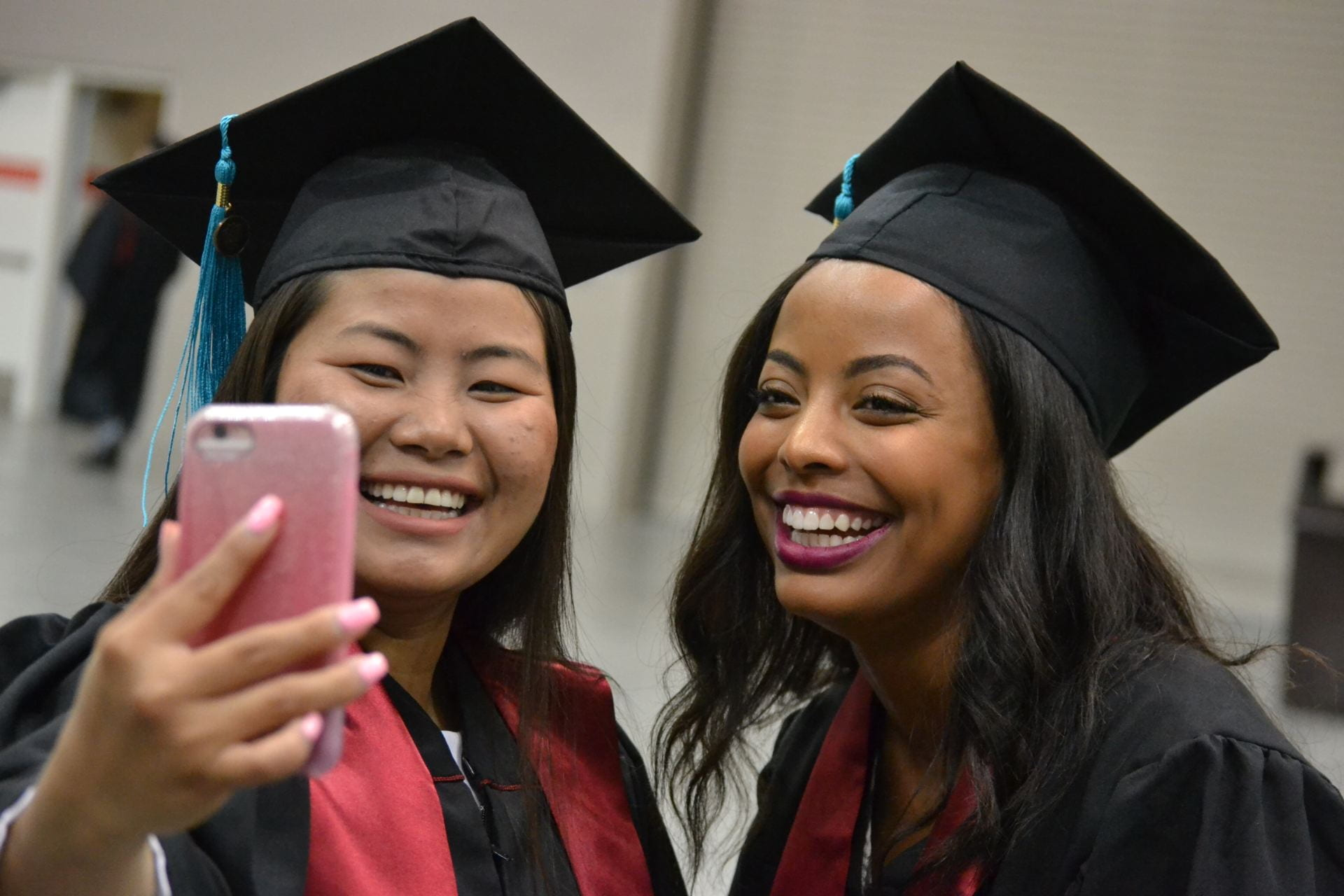Two women in cap and gowns smile and take a picture at commencement.