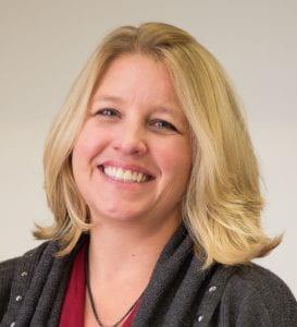 Headshot of Kathy Koehler, blonde hair wearing a gray sweater and red shirt, smiling