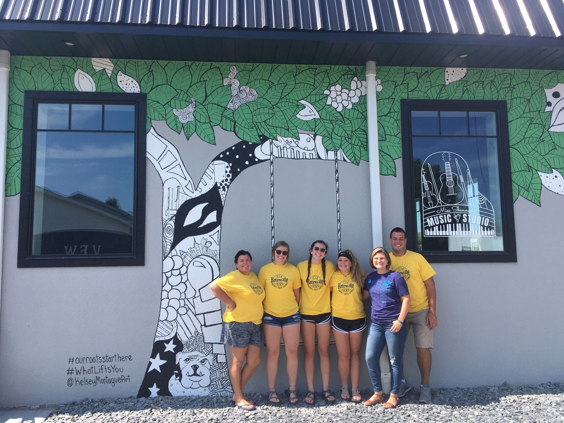 group of teens stand in front of newly painted mural of tree swing.