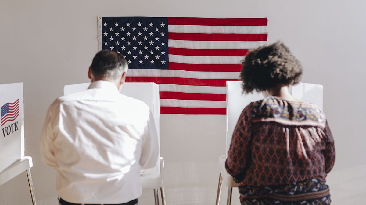 Man and woman standing at voting machines to vote.