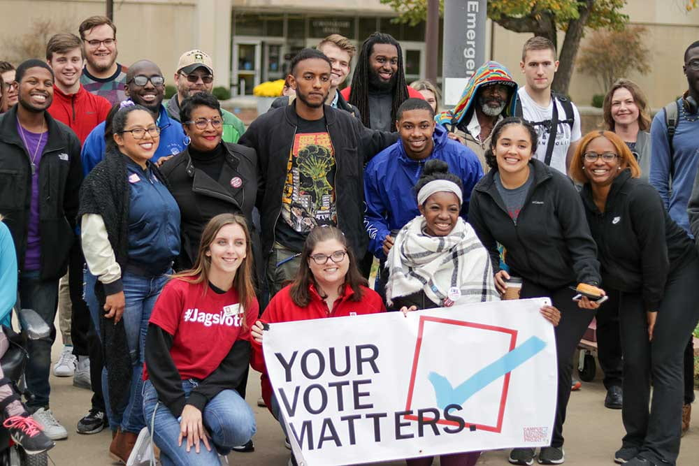 A group of students stands with a sign that says Your Vote Matters