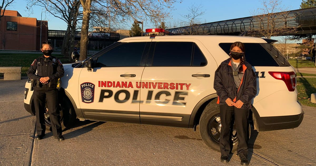 Two students stand outside an IUPD vehicle
