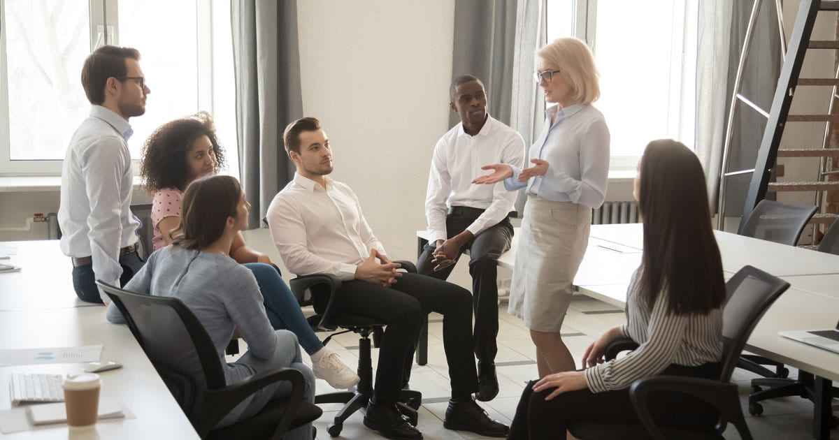 Group of people sitting in a meeting while a woman speaks to the group.