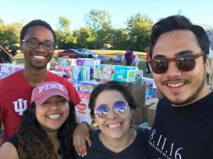 Group of young adults stand at food donation drive
