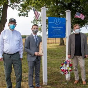 Blue heritage site sign that gives history of Sugar Creek Community