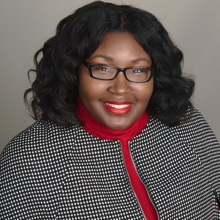 headshot of woman wearing glasses, red shirt, and black/white check jacket