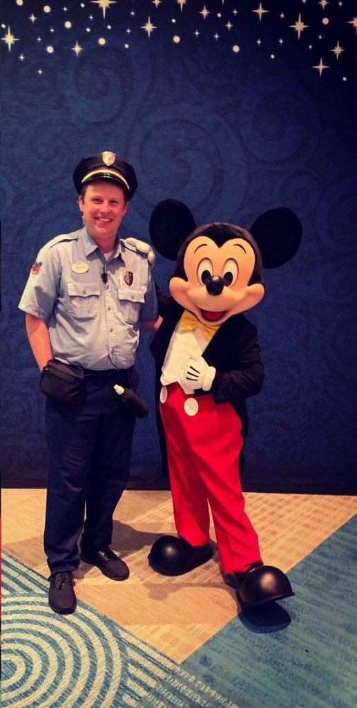 man in security uniform stands with Mickey Mouse