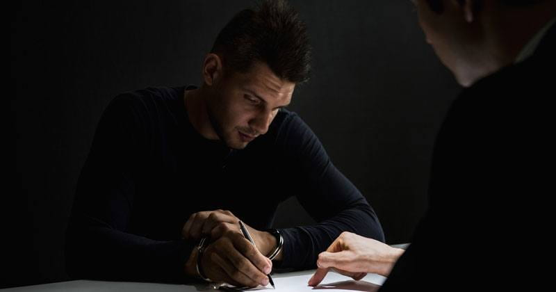 man in handcuffs sitting at desk signing paper