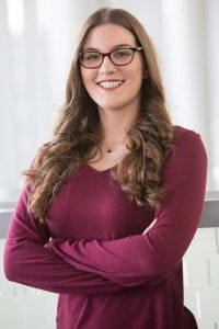 Woman standing with arms crossed, wearing a sweater and glasses with her arms crossed.