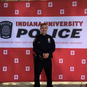 man standing in front of IU police department background wearing a police uniform